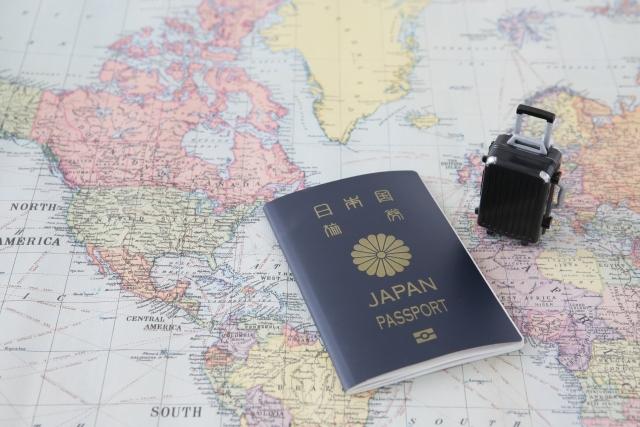 世界地図の上にパスポートとミニチュアバッグ
