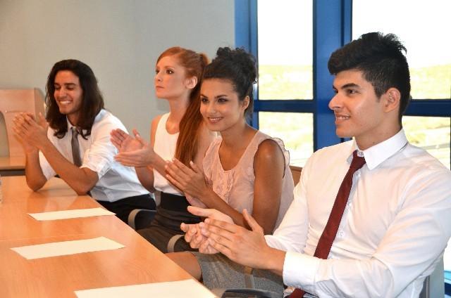 会議で拍手をする外国人たち