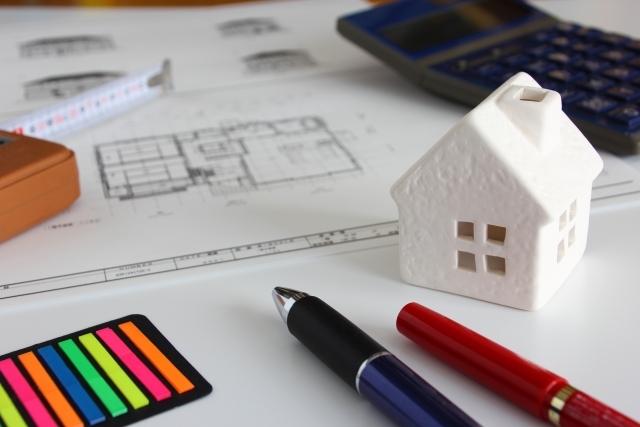 電卓と書類とペンと家の模型